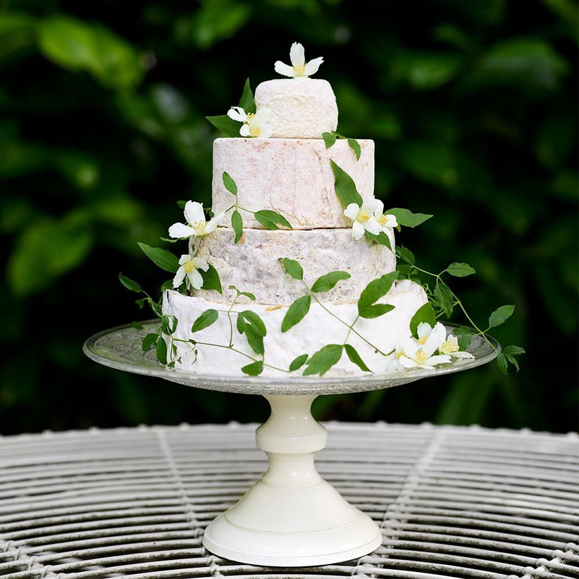 a small cheese wedding cake with white blooms and leaves is a gorgeous idea for a couple who doesn't want any sweets