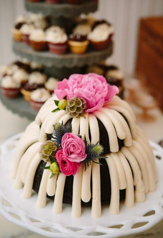 a black two-tier bundt wedding cake with icing, pink blooms and thistles is a lovely and cool idea to rock