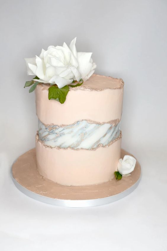 a blush wedding cake with a white marble fault line and a white bloom on top is a chic and beautiful idea to rock