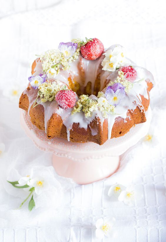 a bundt cake with creamy drip, sugared and dried blooms and berries on top is a lovely idea for a boho wedding