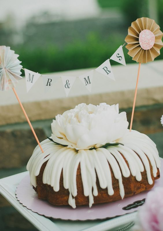 a bundt wedding cake with creamy drip, a large white bloom and a banner with paper fans is simple and cool