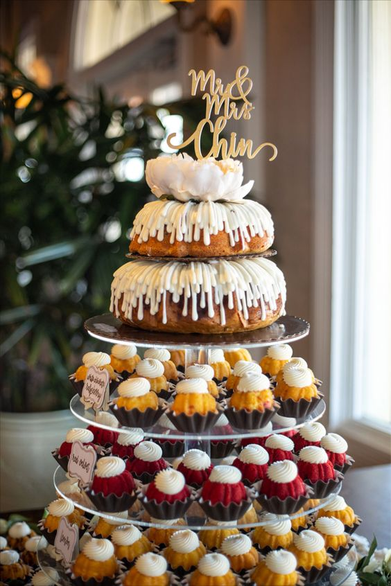 a bundt wedding cake with creamy drip and a large white bloom and a gold calligraphy topper plus lots of cupcakes