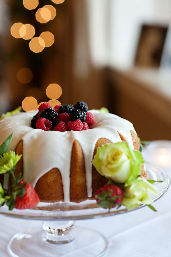 a bundt wedding cake with creamy drip, fresh berries on top and yellow roses and strawberries