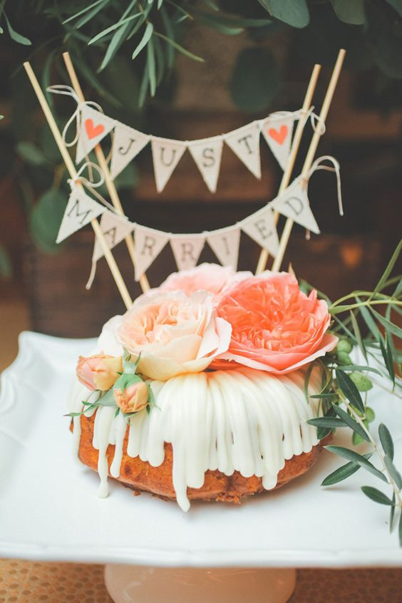 a bundt wedding cake with peachy and orange blooms, greenery and a lovely banner topper for a summer wedding