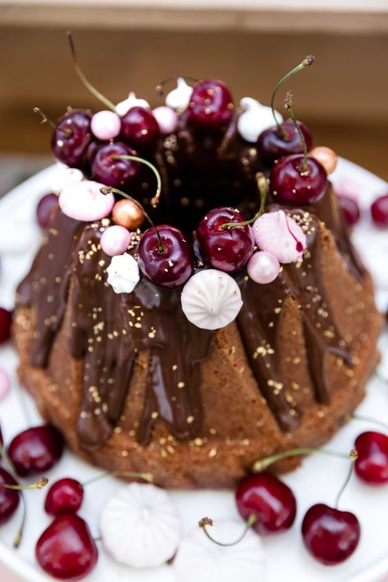 a chocolate bundt wedding cake with chocolate drip, gold leaf, fresh cherries, meringues and beads is a lovely and glam idea
