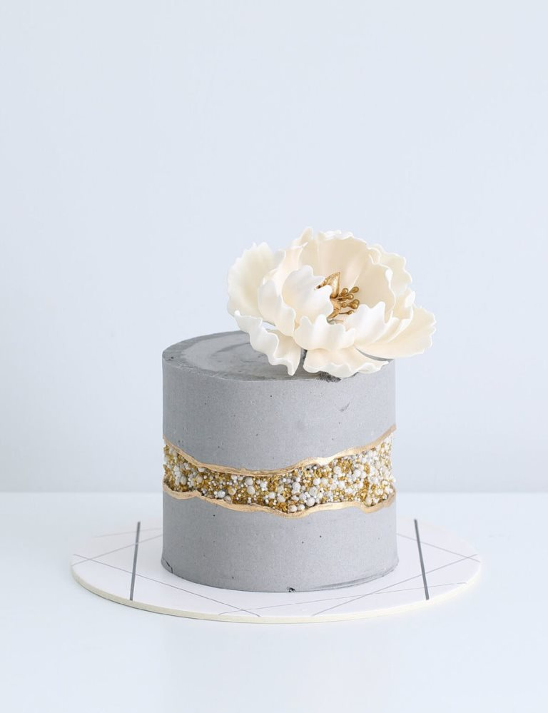 a concrete style wedding cake with a fault line done with gold sparkles and edible beads plus a large white sugar bloom on top