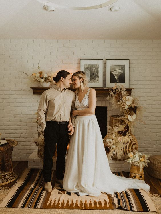 a cozy and intimate at home wedding ceremony at the fireplace, with lush and cool boho wedding decor
