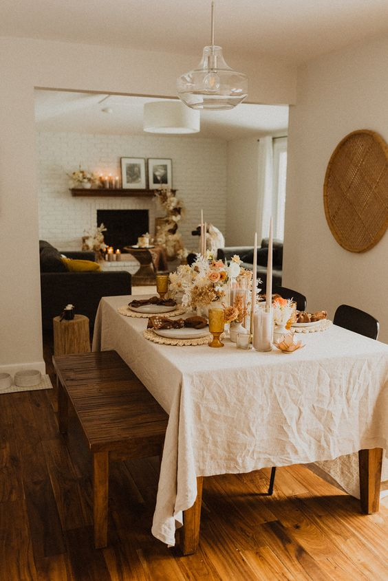 a cozy and small boho wedding reception right in the dining room at home, styled with candles and lush blooms and foliage