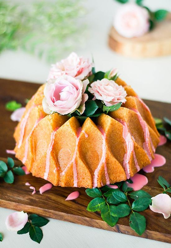 a creatively shaped bundt wedding cake with pink drip, pink blooms and greenery on top for a refined garden wedding