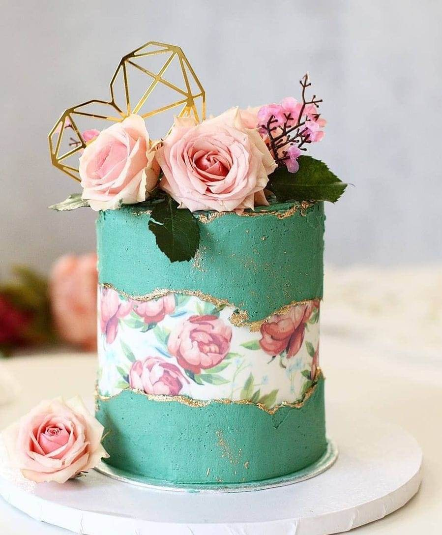 a green matte wedding cake with a floral fault line, some pink blooms and greenery and a gold geometric heart on top