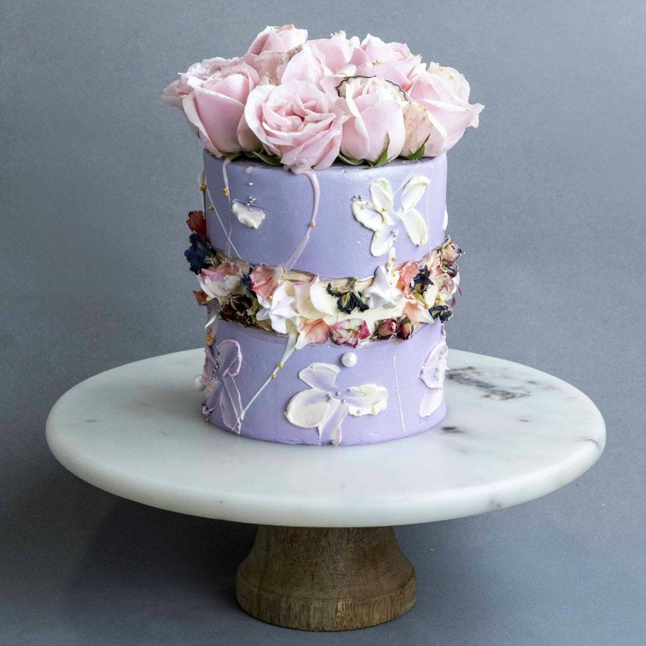 a lilac wedding cake with a fault line done with dried and fresh blooms and with pink roses on top