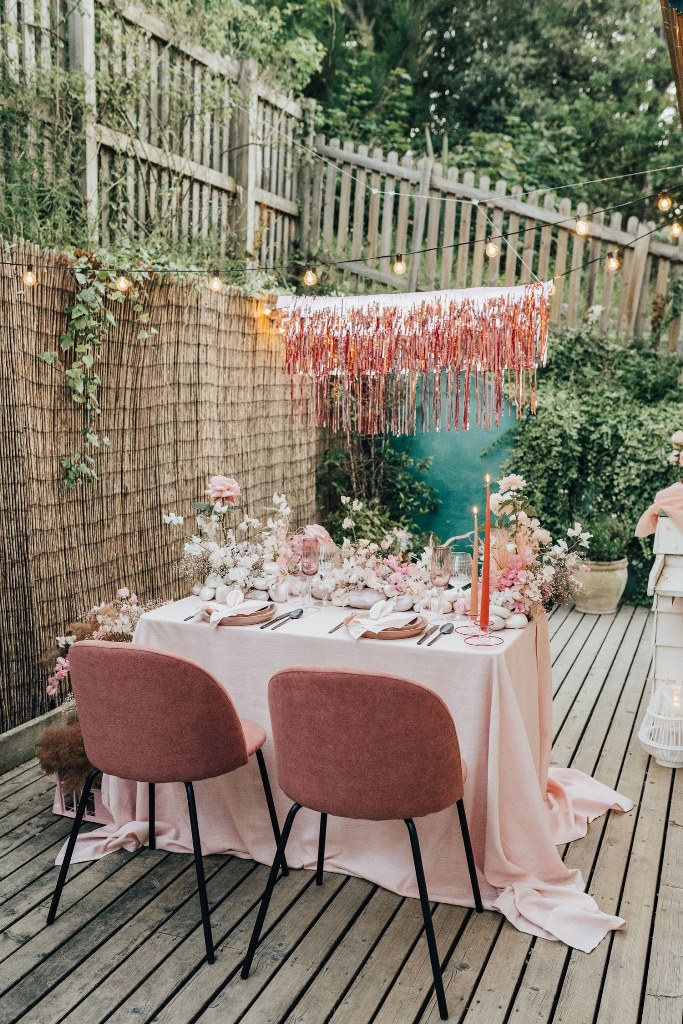 a little pink reception space right on the terrace of the house, with lush floral blooms, shiny fringe and candles