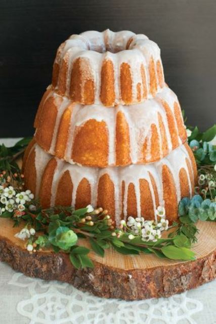 a lovely three-tier bundt wedding cake with creamy drip, white blooms and greenery and served on a large wood slice