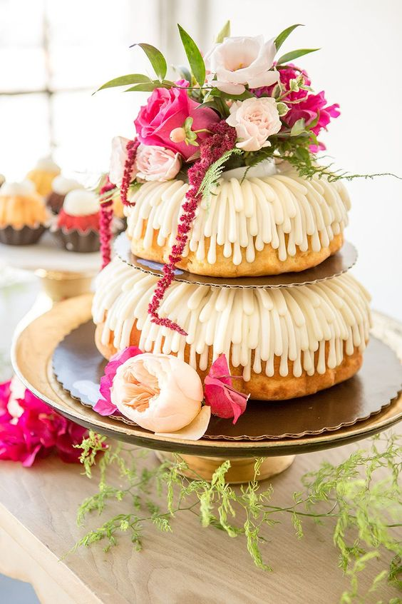 a lovely two-tier wedding cake with creamy drip, blush and hot pink blooms and greenery is a pretty idea for a summer wedding