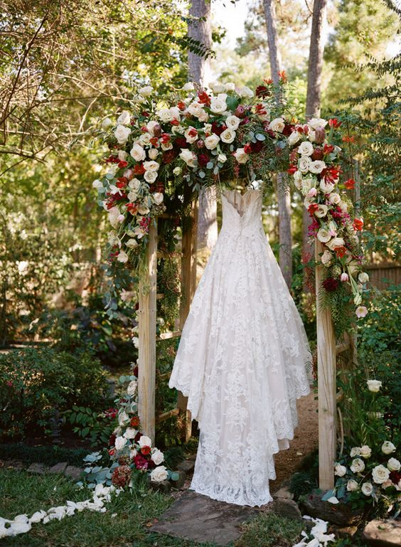 a lush backyard wedding arch with neutral, burgundy and red blooms and greenery showing off the wedding dress