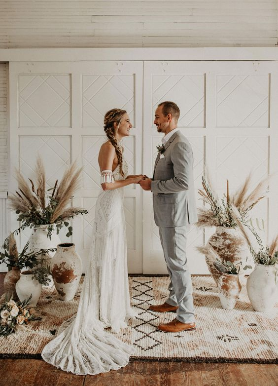 a natural and modern boho wedding at home, with lots of greenery and pampas grass in large shabby chic vases is a stylish idea