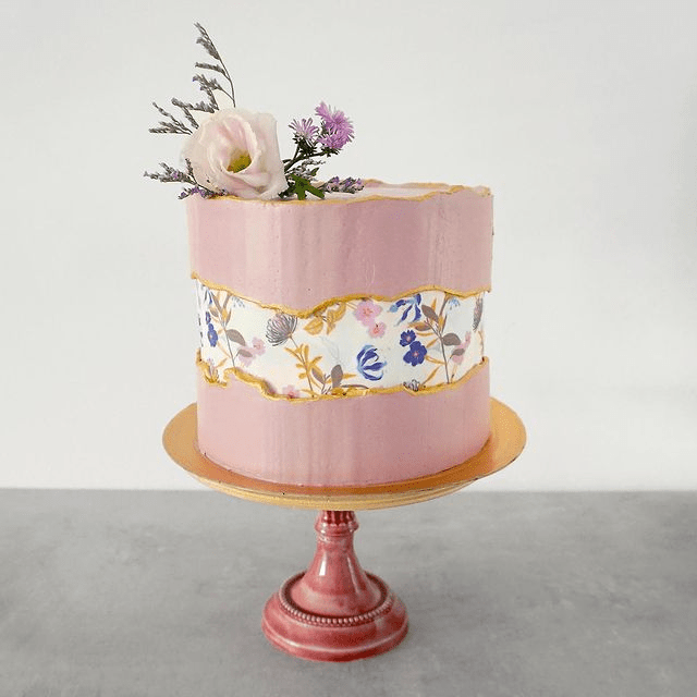 a pink wedding cake with a fault line done with a wildflower pattern and with some matching blooms on top of it