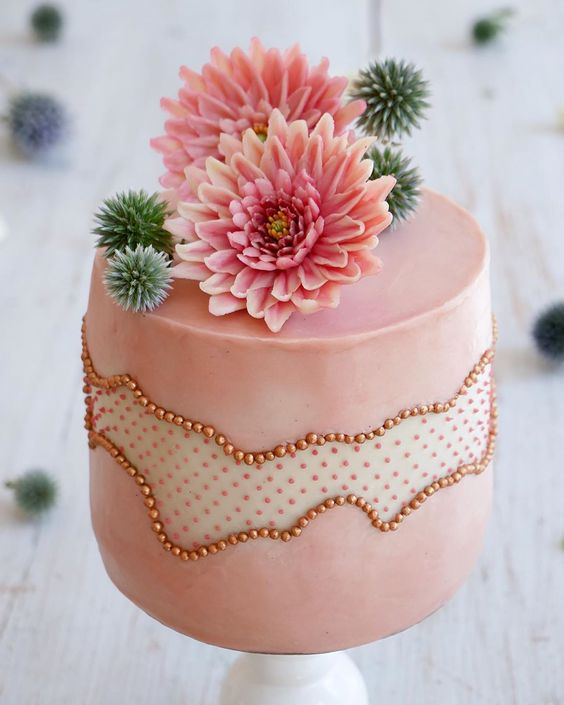 a pink wedding cake with a polka dot fault line and beads, sugar pink dahlias and succulents on top is very pretty