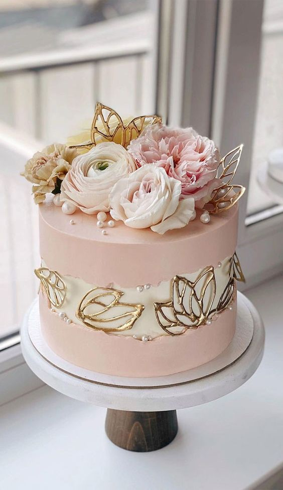 a pink wedding cake with a white fault line and gold leaves plus pearls, pink and white blooms on top