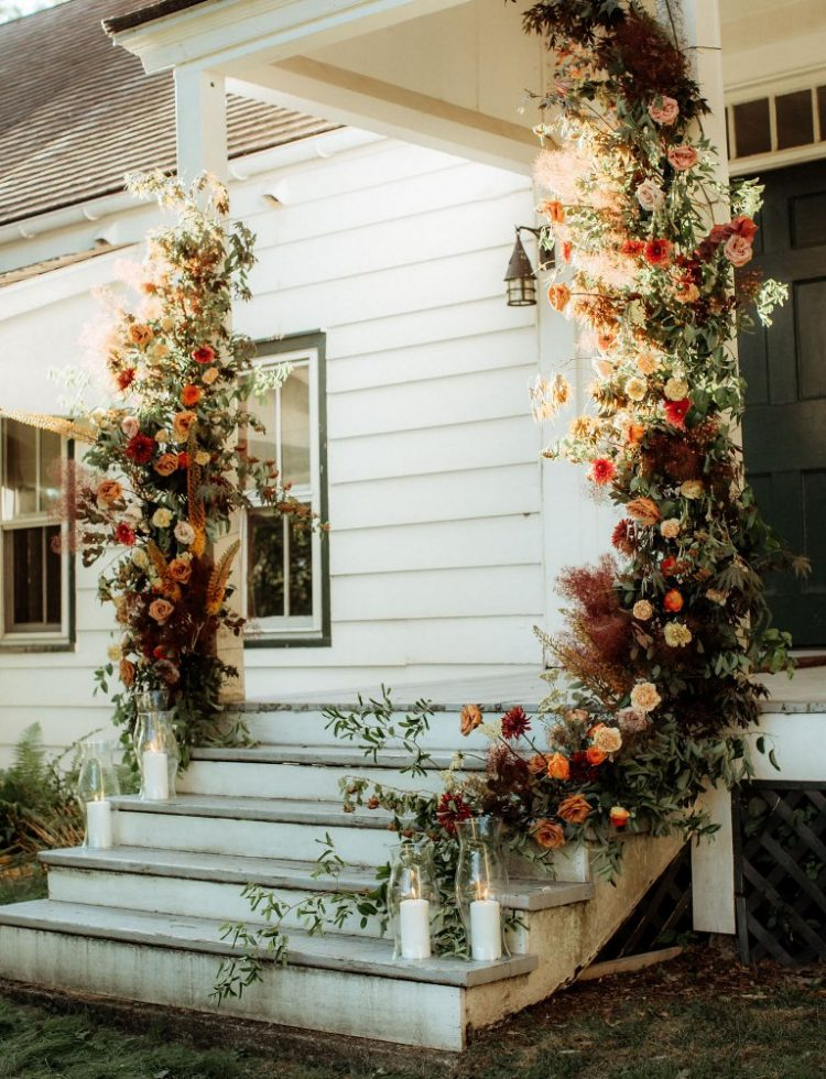 a porch styled with lush florals in bold fall shades, with greenery and candles on the steps is a lovely boho wedding ceremony space