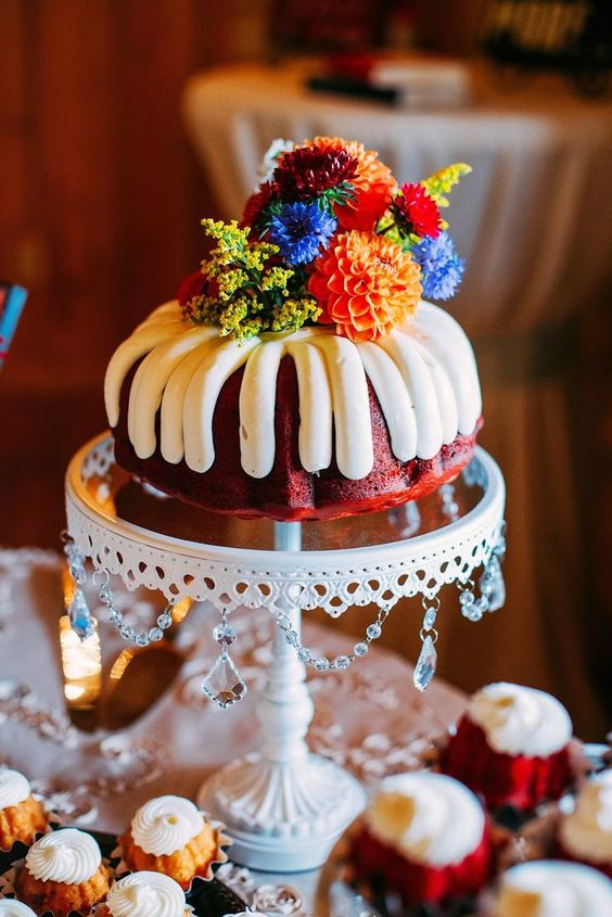 a red velvet bundt wedding cake with frosting topper with colorful blooms for a summer wedding