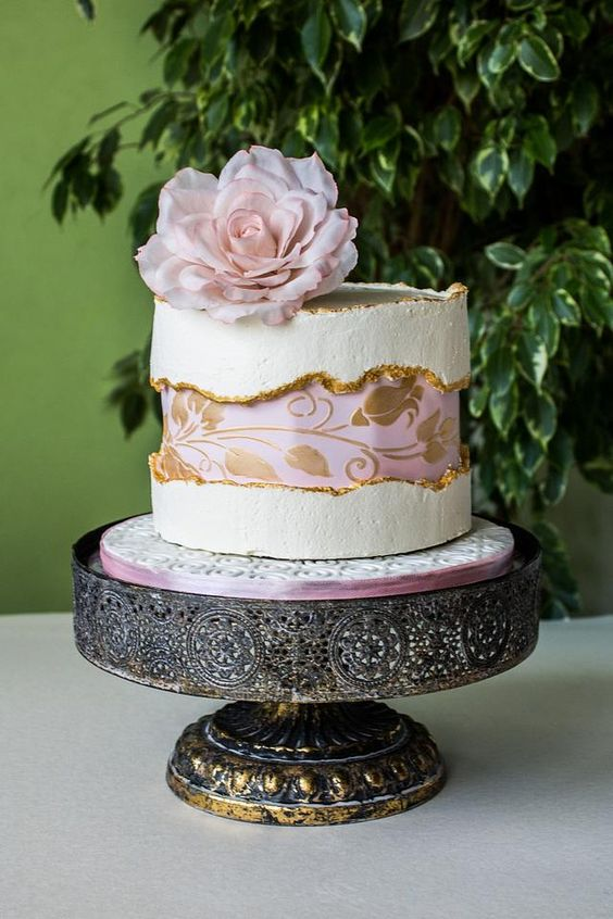 a refined white wedding cake with a pink and gold floral fault line, a gold edge and a pink bloom on top