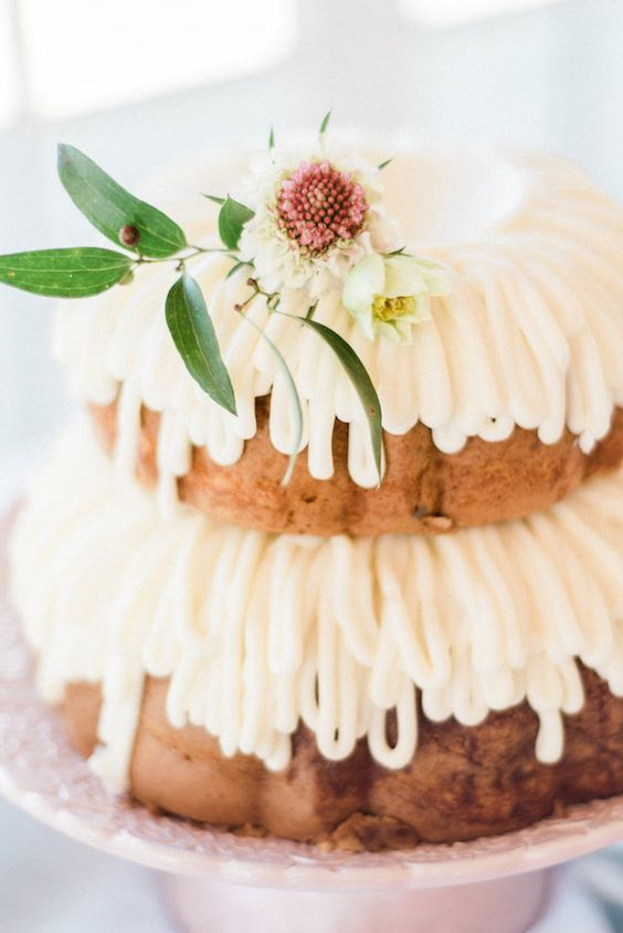 a simple two-tier bundt wedding cake with frosting and white blooms and foliage is amazing