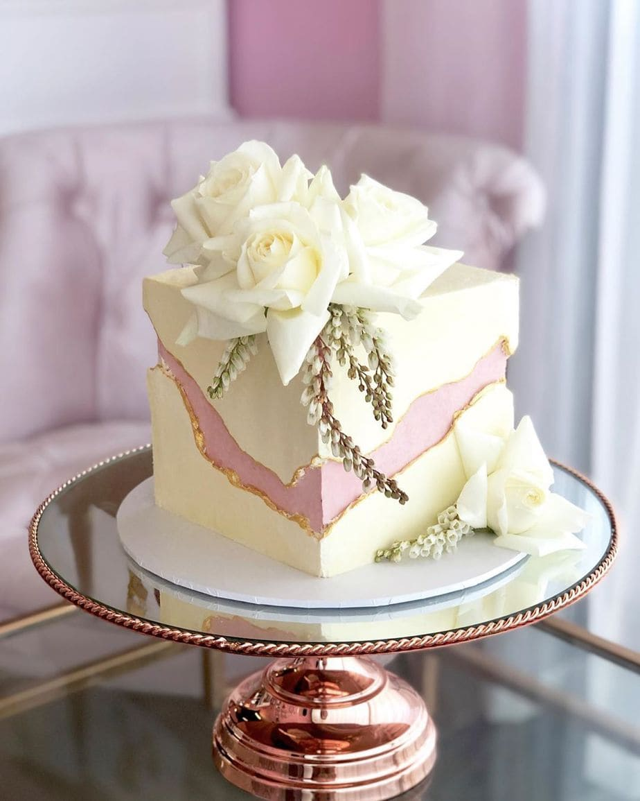 a square fault line wedding cake with an irregular pink part and big white blooms on top and around it