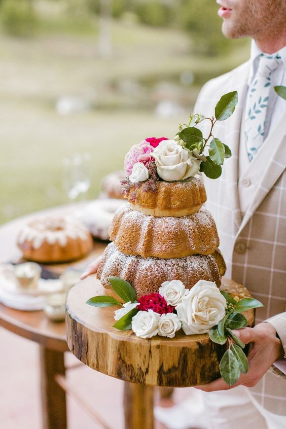 a three-tier bundt cake cake with white and pink blooms and greenery is a very pretty idea