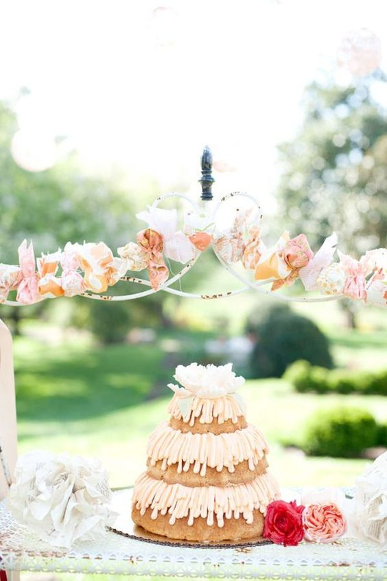 a three-tier bundt wedding cake with peachy frosting and a large white bloom on top for a summer wedding