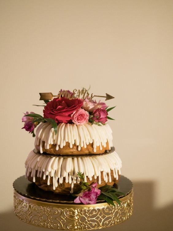 a tow-tier budnt wedding cake with icing, pink and red blooms and a gold arrow topper for a simple wedding