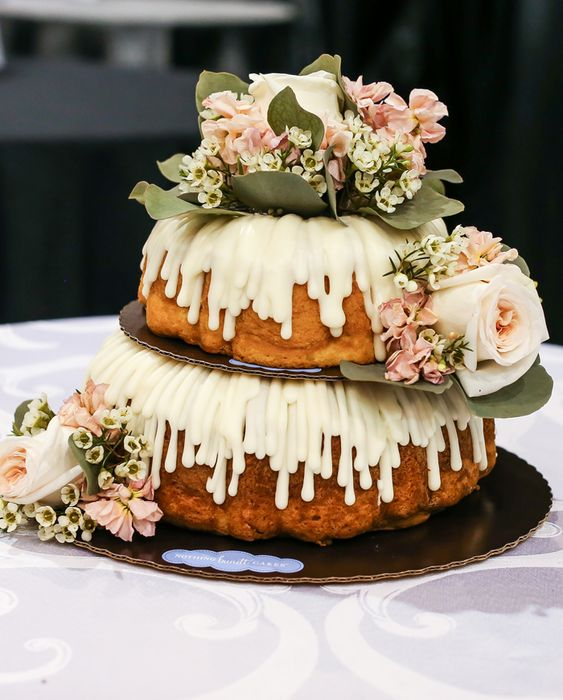 a two-tier bundt wedding cake accented with foliage and blush blooms is a lovely and relaxed wedding dessert idea