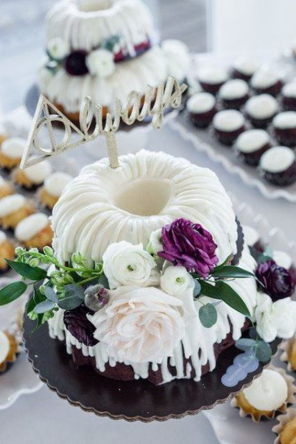 a two-tier bundt wedding cake with creamy drip, blush, white and purple blooms and greenery and a metallic topper