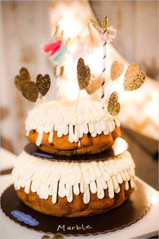 a two-tier bundt wedding cake with creamy drip, gold glitter heart toppers and a tassel banner on top