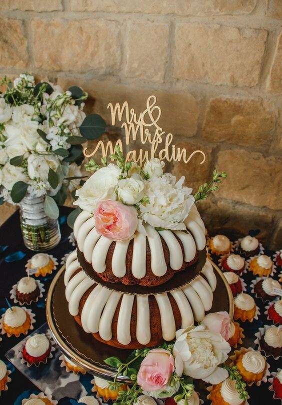 a two-tier bundt wedding cake with creamy drip, pink and white blooms and a gold calligraphy topper