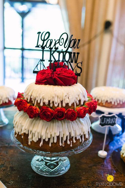 a two-tier bundt wedding cake with creamy drip, red roses and a cool and fun quote topper