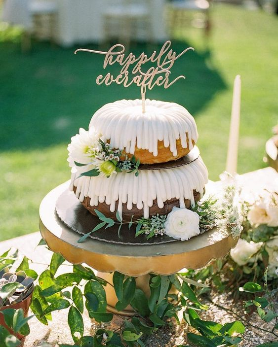 a two-tier bundt wedding cake with creamy drip, white blooms and greenery and a gold calligraphy topper