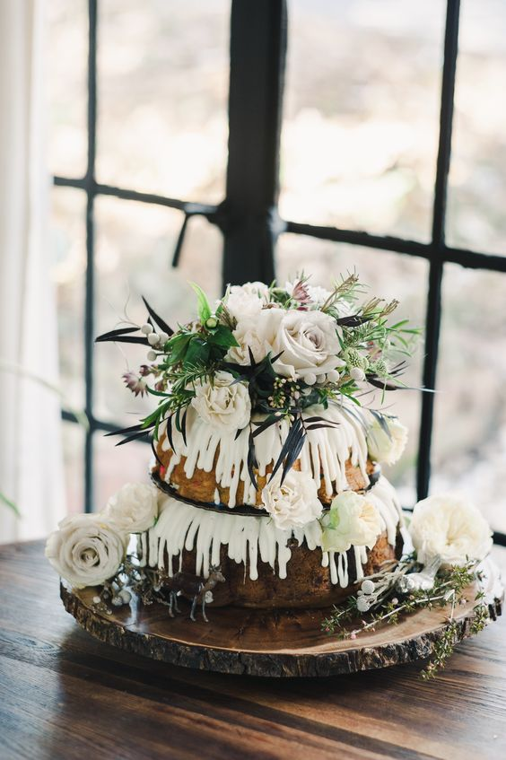 a two-tier bundt wedding cake with creamy drip, white blooms and greenery served on a wood slice with greenery for a woodland wedding