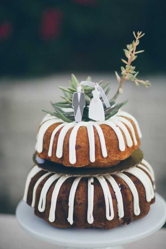 a two-tier bundt wedding cake with creamy drip, with greenery and mini cardboard cake toppers is a lovely idea