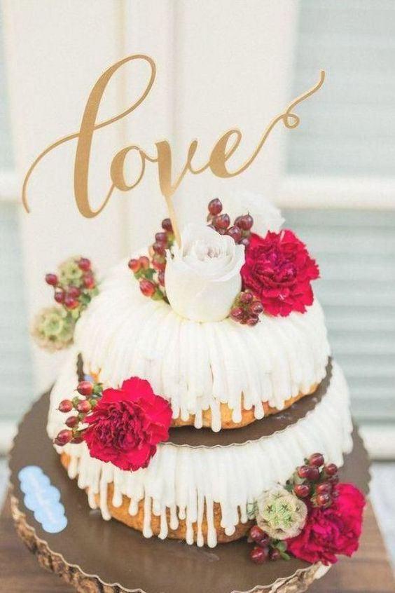 a two-tier bundt wedding cake with drop, white and red blooms and berries, a gold calligraphy topper