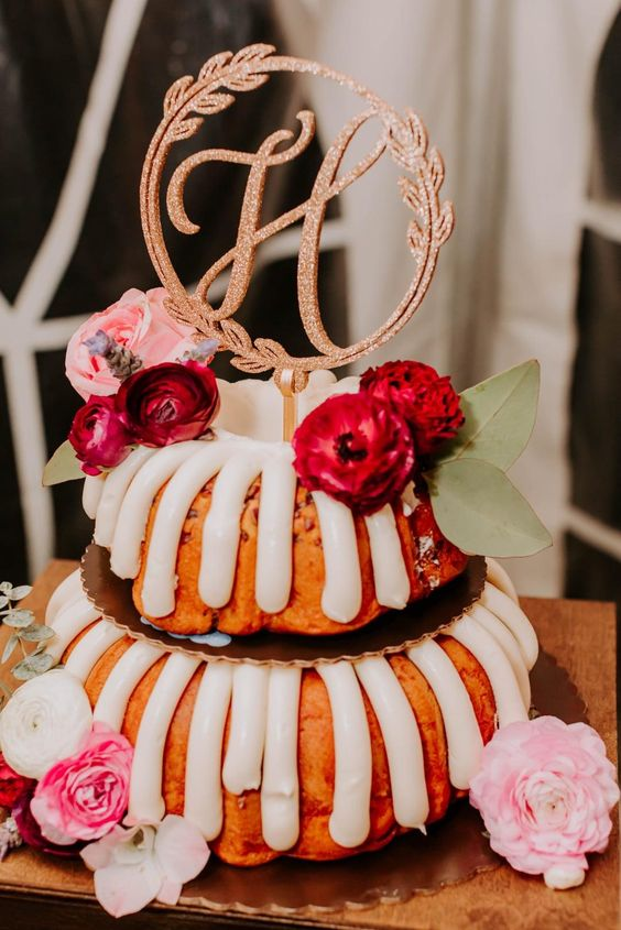 a two-tier bundt wedding cake with frosting, pink and burgundy blooms and foliage and a copper glitter topper