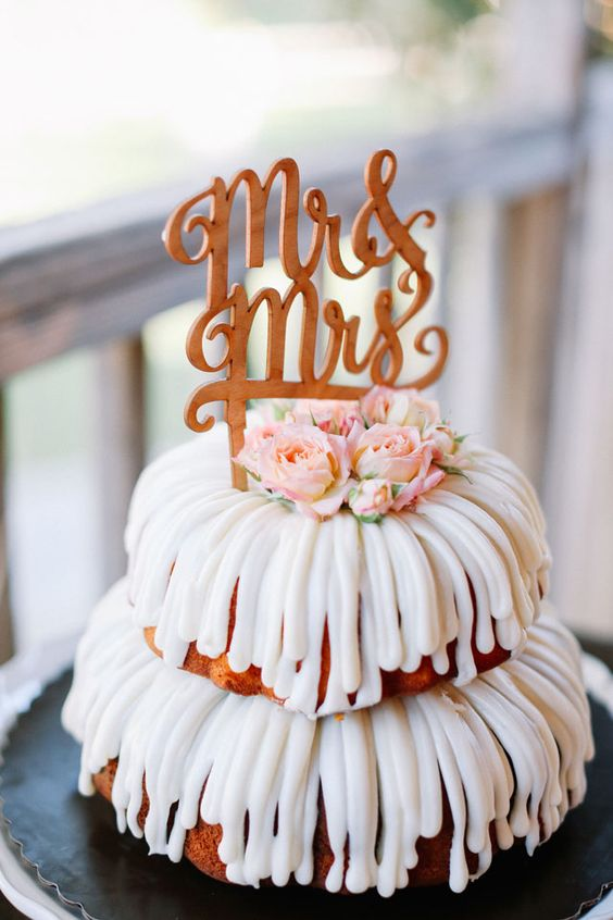 a two-tier bundt wedding cake with icing, pink blooms and a calligraphy topper for a laid-back wedding