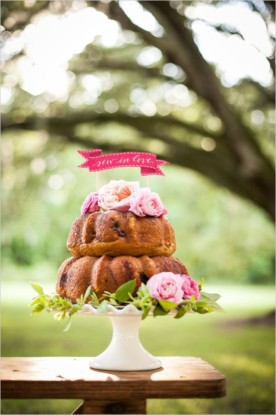 a two-tier bundt wedding cake with pink blooms and greenery and hot pink topper is a stylish and bold idea