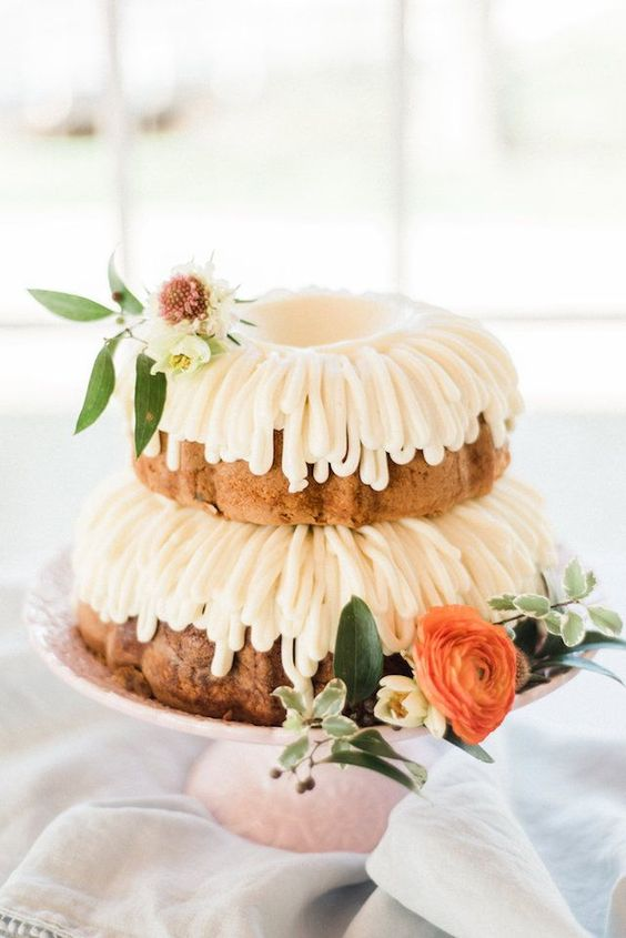 a two-tier bundt wedding cake with white and orange blooms and greenery is a pretty idea for a spring or summer wedding