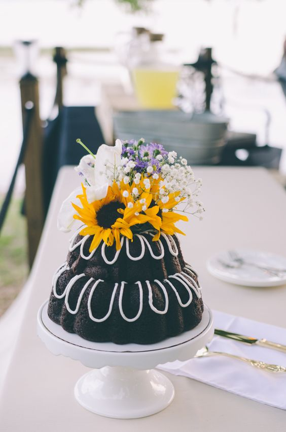 a two-tier chocolate bundt wedding cake with drip, bright blooms on top for a relaxed rustic or backyard wedding