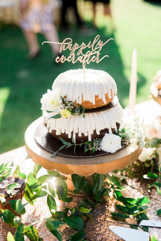 a two-tier vanilla and chocolate bundt wedding cake with icing, white blooms and greenery and gold calligraphy topper