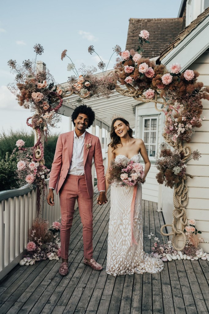 a wedding arch with lush pink blooms and grasses, with pebbles and rope created right on the terrace of the house