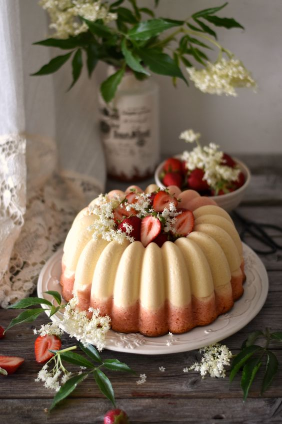 a white and pink bundt wedding cake with white blooms and fresh strawberries inside and on top is gorgeous