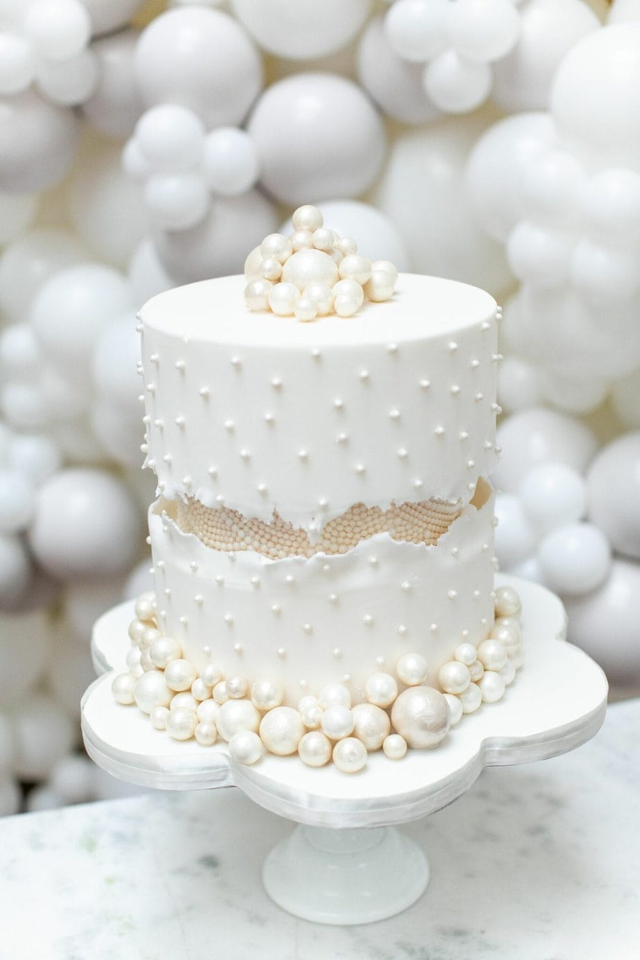 a white beaded wedding cake with a fault line covered with small pearls and with large pearls at the base and on top