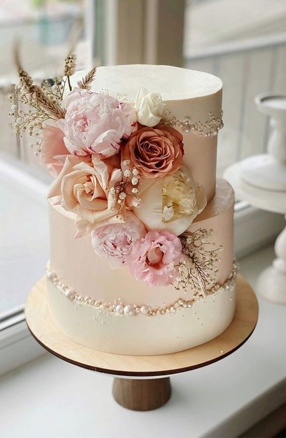 a white wedding cake with a blush fault line covered with beads and pearls and decorated with neutral and pastel blooms